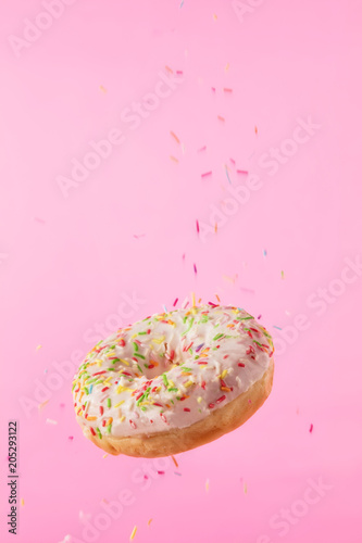 Flying sweet donut isolated on pink background