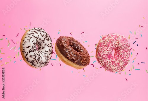 Flying sweet donuts isolated on pink background.