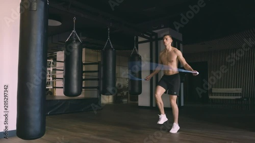Wall mural Athletic man skipping with a jump rope. Slow motion