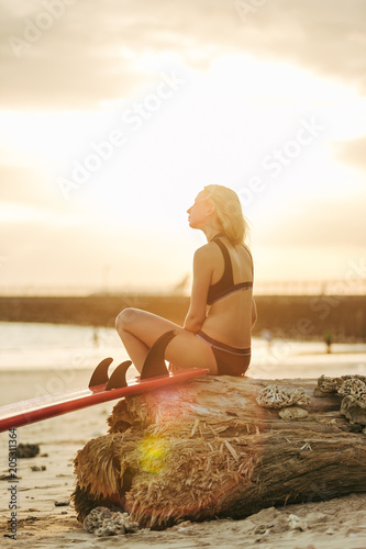 female surfer posing with surfboard on beach at sunset with backlit
