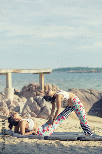 Poster two asian woman playing yoga pose on sea beach