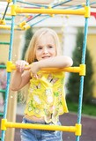 Girl playing on playground in city park - 205323709