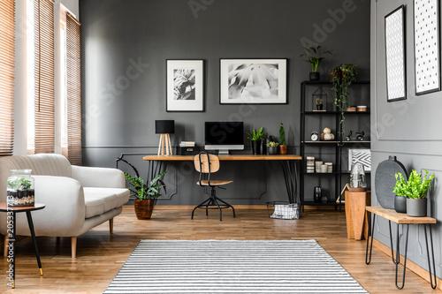 Leinwandbild Motiv Real photo of open space apartment interior with beige sofa next to the window and desktop computer o a wooden desk