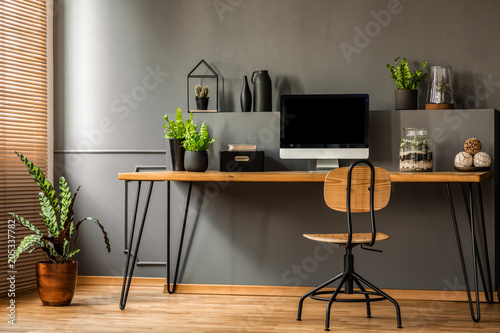 Simple workspace interior with wooden chair at the desk standing against black wall in a room with plants. Real photo
