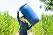 Young Asian farmer carry blue water tank (fermented water tank) for watering in Napier grass field
