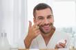 Leinwanddruck Bild - Positive mood. Delighted cheerful man smiling while applying facial cream