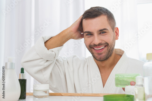 Stylish look. Positive handsome man holding a bottle of hair gel while standing in front of the mirror