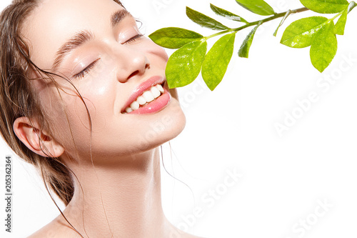 Beautiful woman portrait with fresh wet skin and green plant.