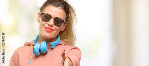 Wall mural Young sport woman with headphones and sunglasses sick and coughing, suffering asthma or bronchitis, medicine concept