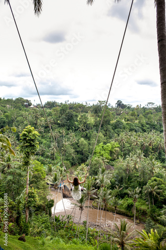 Fotobehang Bali Young tourist woman swinging on the cliff in the jungle rainforest and river of a tropical Bali island. Swing among two palms tree. Back rear view