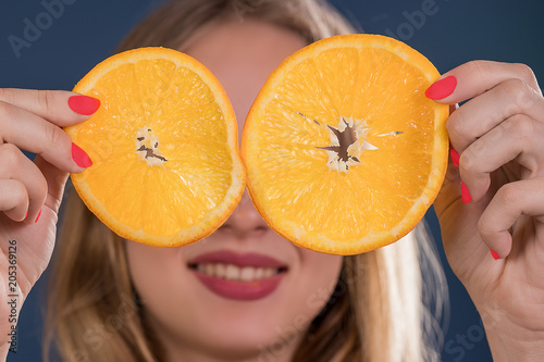 Young girl with sliced round orange slices at eye level.