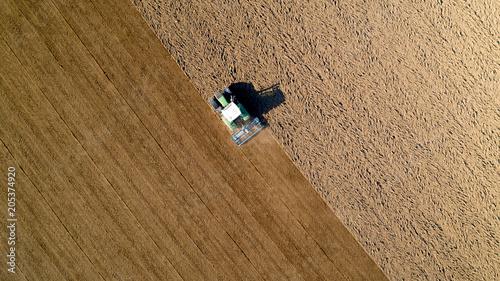Fotobehang Trekker Tracteur labourant un champ dans la campagne, France