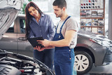 A man mechanic and woman customer discussing repairs done to her vehicle - 205383571