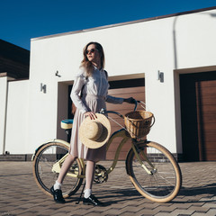 Pretty girl in hat and dress by cruiser bicycle in suburb