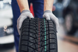 Closeup of mechanic hands pushing a black tire in the workshop - 205384175