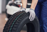 Closeup of mechanic hands pushing a black tire in the workshop - 205384191