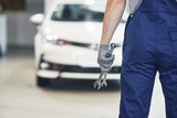 Hands of car mechanic with wrench in garage - 205384307