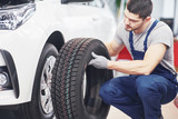 Mechanic holding a tire tire at the repair garage. replacement of winter and summer tires - 205384709