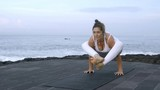 Flexible mature woman in white doing firefly yoga pose, then transitioning into split while training on coastline in morning - 205387553