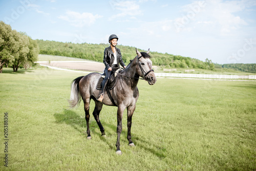 Fototapeta Woman in leather jacket with protective helmet riding a horse on the green meadow