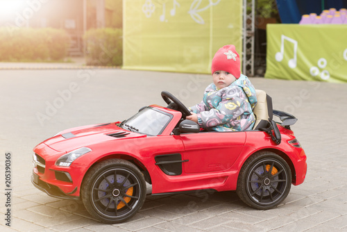Fotobehang Amusementspark A child is riding an electric car