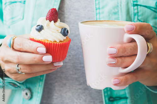 Poster Woman with a cup of cappuccino and a piece of dessert on the plate, soft focus background