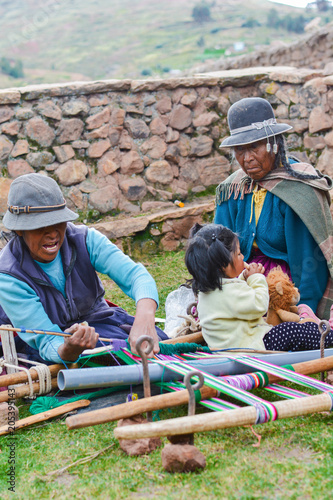 Three generations of native american women in the countryside weaving authentic aymara cloth.