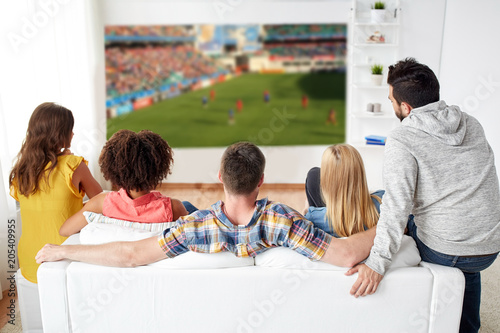 sport, leisure and entertainment concept - friends or football fans watching soccer game on projector screen at home