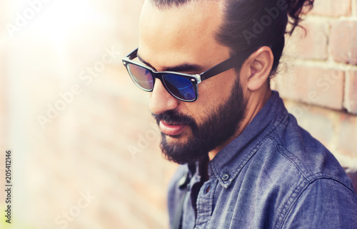 lifestyle, emotion, expression and people concept - man with beard and sunglasses on city street