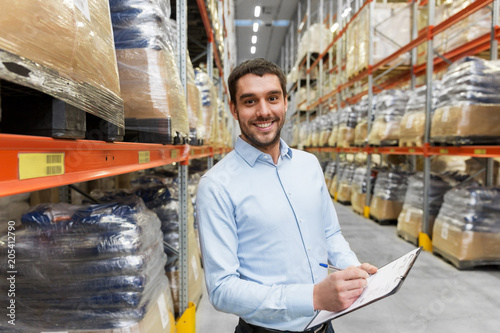 logistic business, shipment and people concept - happy businessman with clipboard at warehouse