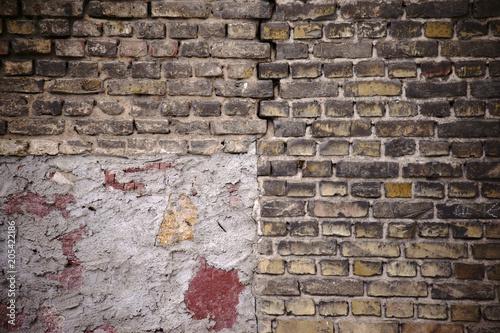 Fototapeta Einsturzgefährdete Ziegelsteinmauer / Eine rustikale und einsturzgefährdete Mauer aus versetzten und abgebrochenen Ziegelsteinen mit einem Riss sowie Ausbesserungsstellen.