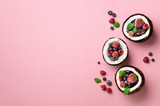 Coconut ice cream with fresh berries in coconuts halves on blue background with copy space. Top View. Pop art design, creative summer concept. Food in minimal flat lay style.