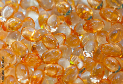 Background - close up of countless colourful orange medicine pills with shallow depth of field, bokeh