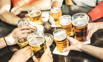 Friends hands drinking beer at brewery pub restaurant - Friendship concept with young people enjoying time together and having genuine fun at cool vintage brew bar - Focus on middle right small glass