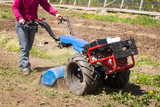 Woman worker driving rototiller tractor unit preparing soil seedbed on outdoor garden