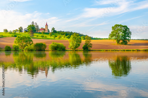 Fotobehang Zomer Romantic landscape with small church on the hill reflected in the pond. Sunny summer day with blue sky and white clouds. St. Peter and Pauls church at Bysicky near Lazne Belohrad, Czech Republic.