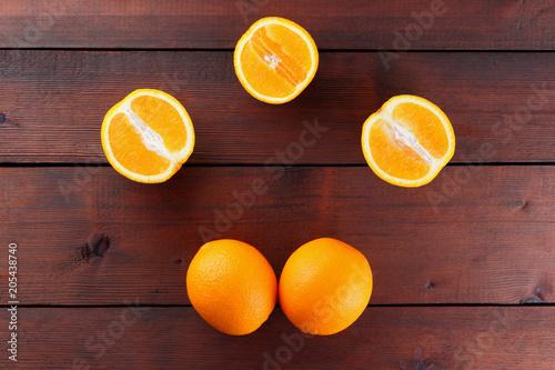 Fruits of oranges on a dark brown wooden background, halves of oranges on wooden boards. Copy space. Orange fruits for vegans. Citrus for breakfast