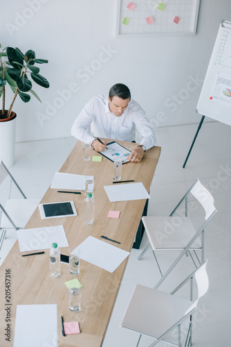 Wall mural high angle view of businessman in formal wear working with papers at workplace in office