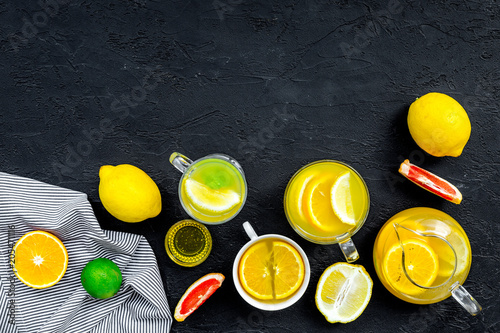 Orzeźwiająca letnia herbata z owocami. Teacup i czajniczek w pobliżu pomarańczy, limonki, cytryny, grejpfruta na czarnym tle widok z góry miejsca na tekst