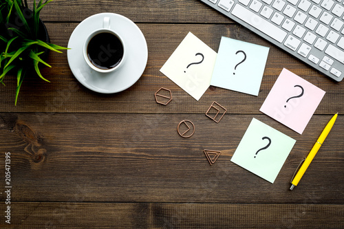 canvas print picture Question mark on sticky notes on office desk on dark wooden background top view copy space. FAQ concept. Working with clients. Troubles in work.