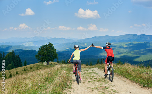 Back view of active couple cyclists in professional sportswear and helmets cycling down cross country bikes on the mountain road on summer day. Sporty man and woman giving each other a high five