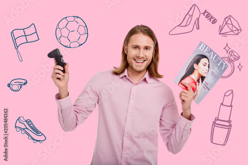 Happy man. Cheerful emotional young man standing with a game console and a fashionable magazine and smiling