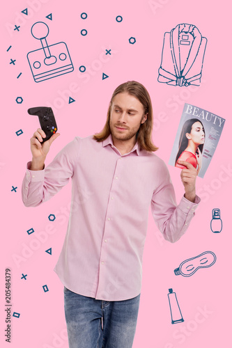 Various interests. Young long haired man in a pink shirt holding a game console and a fashion magazine
