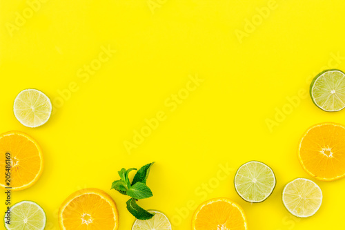 Citrus frame. Oranges and lime round slices composition on yellow background top view copy space