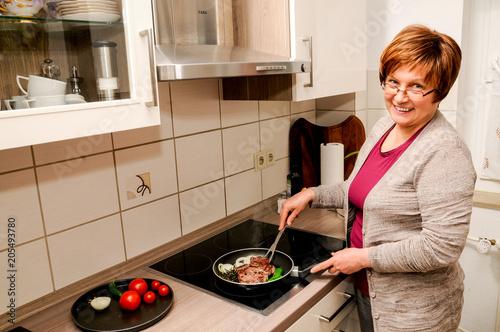 Fotobehang Steakhouse Frau mittleren Alters bereitet Steak zu.