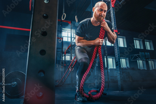 Wall mural Men with battle rope battle ropes exercise in the fitness gym. CrossFit.