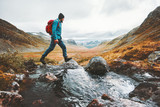 Man solo traveling backpacker hiking in scandinavian mountains active healthy lifestyle adventure journey vacations