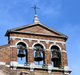 red brick bell tower with three metal bells
