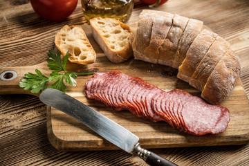 Italian ciabatta bread cut in slices with salami.
