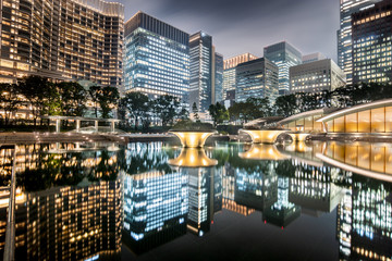 Cityscape in the Marunouchi business district of Chiyoda with skyscrapers reflected in the fountain taken in a cloudy night, Tokyo, Japan